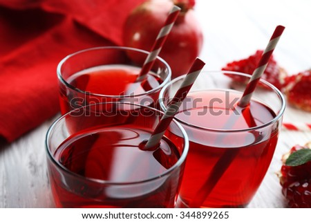 Three glasses of tasty juice and garnet fruit on the table, close-up