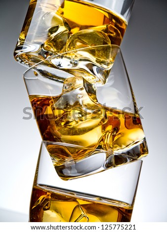Three glasses of whiskey on the rocks, one on top of the other - stock photo