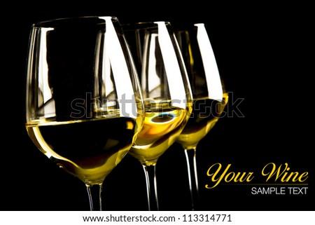 three glasses of white wine on black background - stock photo