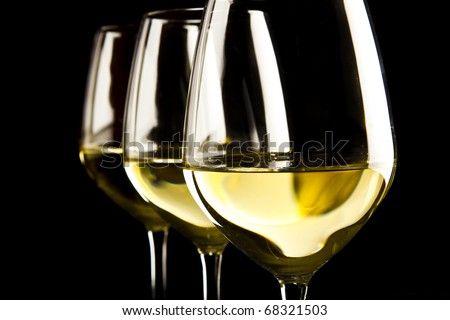 three glasses of white wine on black background - stock photo