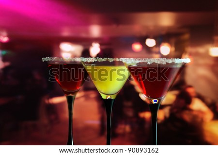 Three glasses with a cocktail in bar. - stock photo