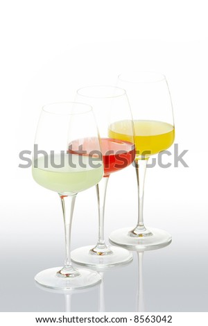 Three glasses with beverages, reflected on gray background