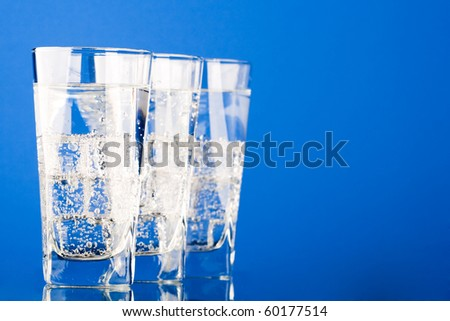 three glasses with cold water on blue background
