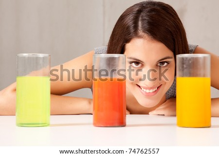 Three glasses with colorful liquid - woman doing experiement - stock photo