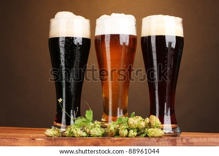 three glasses with different beers and hop on wooden table on brown background - stock photo