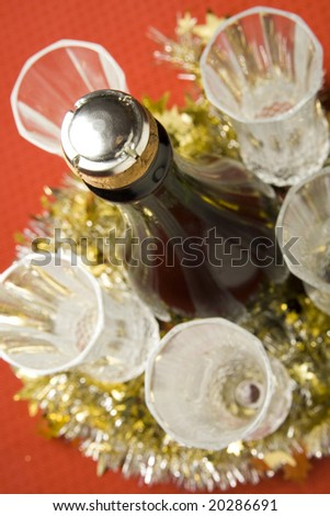 Three glasses with wine bottle and Christmas decoration on red background.