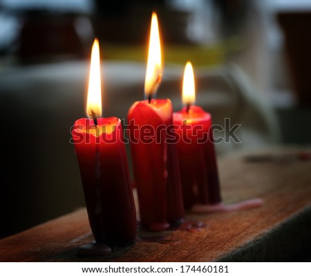 Three glowing candles close up, shallow dof