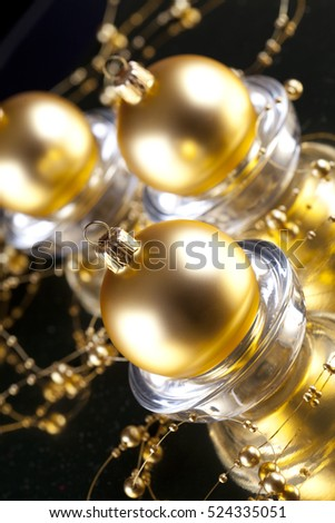 Three gold baubles on black background