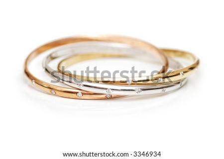 Three gold bracelets  isolated on the white - stock photo