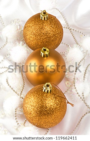Three gold Christmas baubles on white silk.