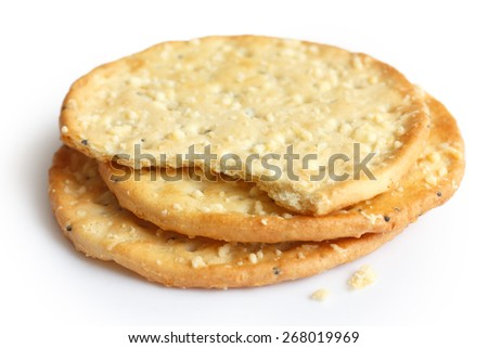 Three golden cheese crackers on white.