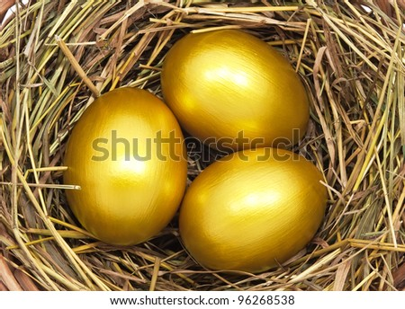Three golden eggs in the hay nest - stock photo