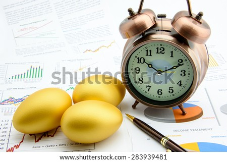 Three golden eggs with a clock on business and financial reports : Investment concept  - stock photo