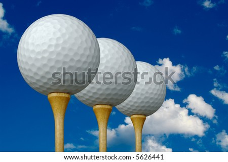 Three Golf Balls & Tees on the left with clouds and sky background. - stock photo