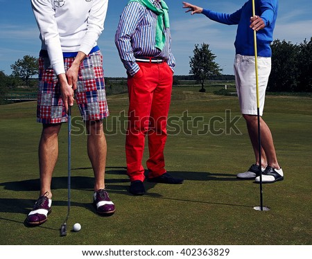 Three golf players on green field under blue sky.