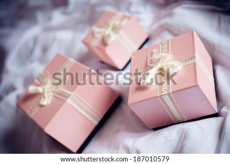Three gorgeous beautiful luxury boxes pink presents with white ribbon on white bed background - stock photo