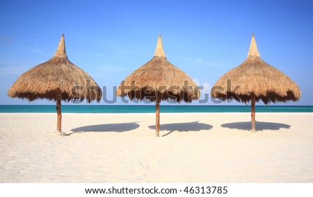 Three grass umbrellas on a resort beach - stock photo