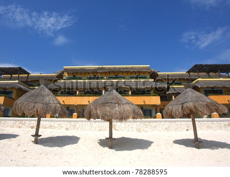 Three grass umbrellas on a resort beach - stock photo