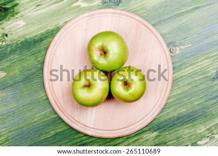Three green apple on a cutting board, right on the table, top view  - stock photo