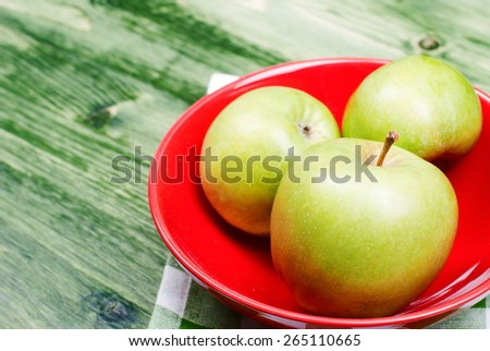 Three green apple on the red plate on a table with green cloth  - stock photo