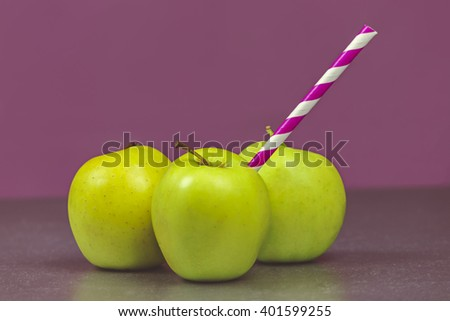 Three Green Apples with Striped Straw on Purple Background