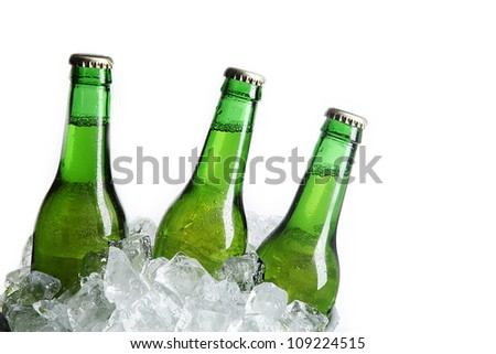 Three Green Beer Bottles in Ice Bucket with Condensation isolated on white - stock photo