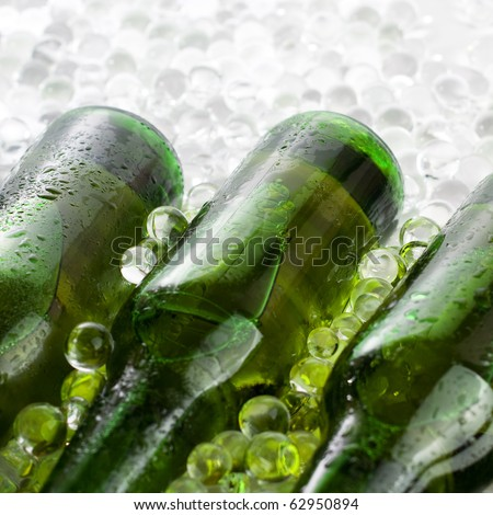 three green beer bottles in the ice - stock photo