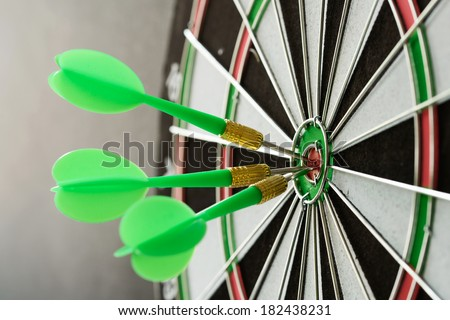 Three green darts pinned on the center of dartboard - stock photo