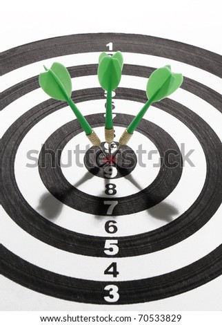 three green darts smack in the center of the board - stock photo