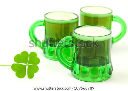 Three green glasses filled with beer with foam at the top and a four-leaf clover in the foreground on a white background - stock photo