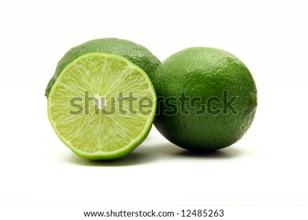 Three green juicy limes isolated on white background, one cut in half - stock photo