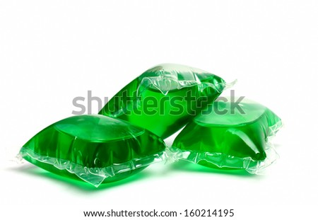 Three green laundry detergent capsules on white - stock photo