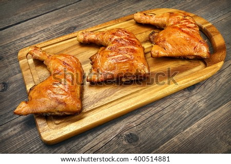 Three Grilled BBQ Crispy Chicken Leg Quarter On The Wood Board And Country Table In The Background, Top View, Closeup - stock photo