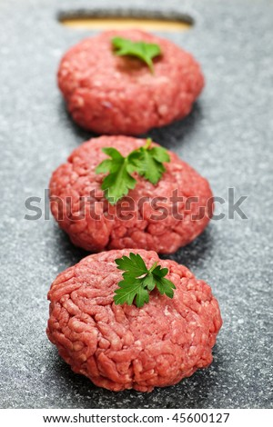Three ground beef hamburger patties on cutting board - stock photo