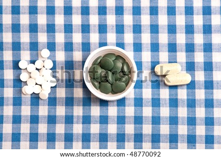 Three groups of pills on a blue and white checkered table cloth. - stock photo