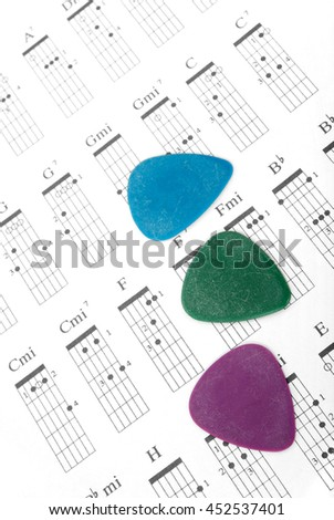 Three guitar picks on of different colors a chords chart.