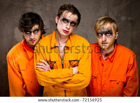 Three guys in orange uniforms indoors - stock photo