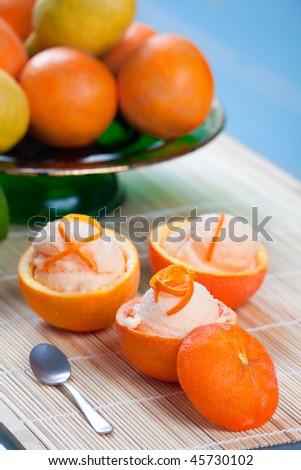 Three hallowed oranges filled with fresh italian orange sorbet on a japanese towel. - stock photo