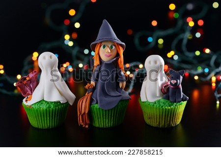 Three Halloween cupcakes decorated with sugar figures of witch and ghosts. - stock photo