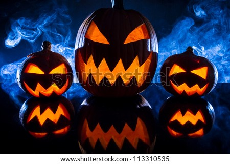 Three halloween pumpkins in the smoke background - stock photo