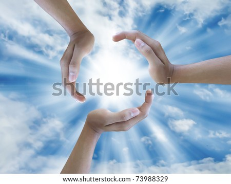 three hand holding the sun - stock photo