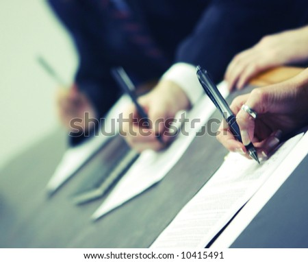 three hands holding pens signing document on table - stock photo