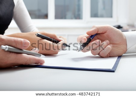 Three hands with pens over document