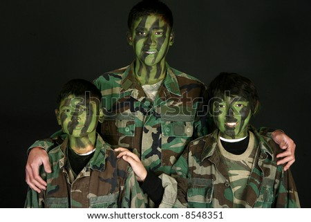 Three handsome Filipino brothers in camo paint and fatigues over black. - stock photo