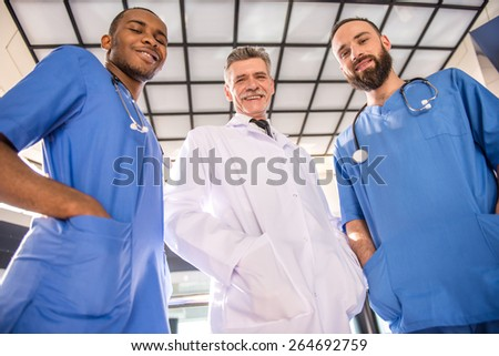Three handsome male doctors looking at camera in hospital. - stock photo