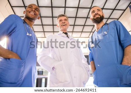 Three handsome male doctors standing in hospital. - stock photo