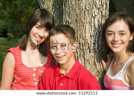 Three happy adolescents standing by a tree in the afternoon sun. - stock photo