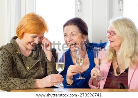 Three Happy Adult Female Friends Laughing at their Funny Conversation About their Past at the Table with Glasses of White Wine. - stock photo