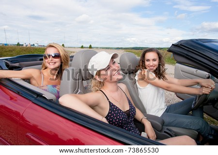 three happy and sensual caucasian girlfriends having preparing for a drive on a red cabriolet car with bright positive expressions. shoot made on location with strobes