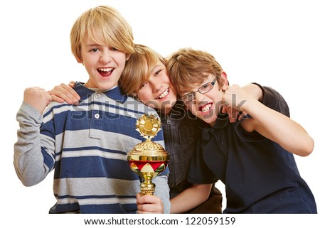 Three happy boys with a trophy cheering with clenched fists - stock photo
